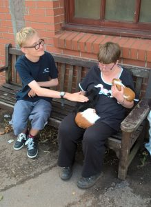 Lewis pets the guinea pigs at Elm Tree Farm